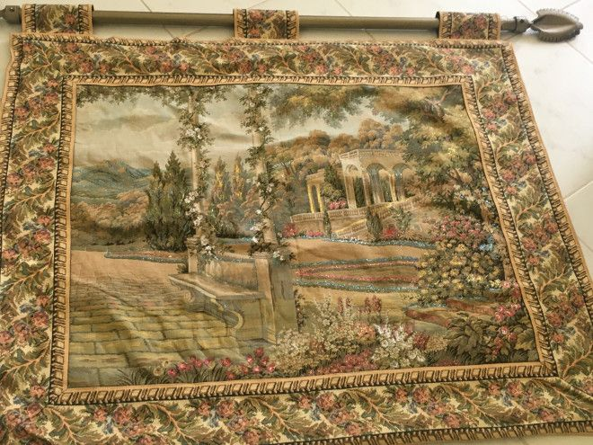 Console with pictures. Oatman with carpet hanged on the wall